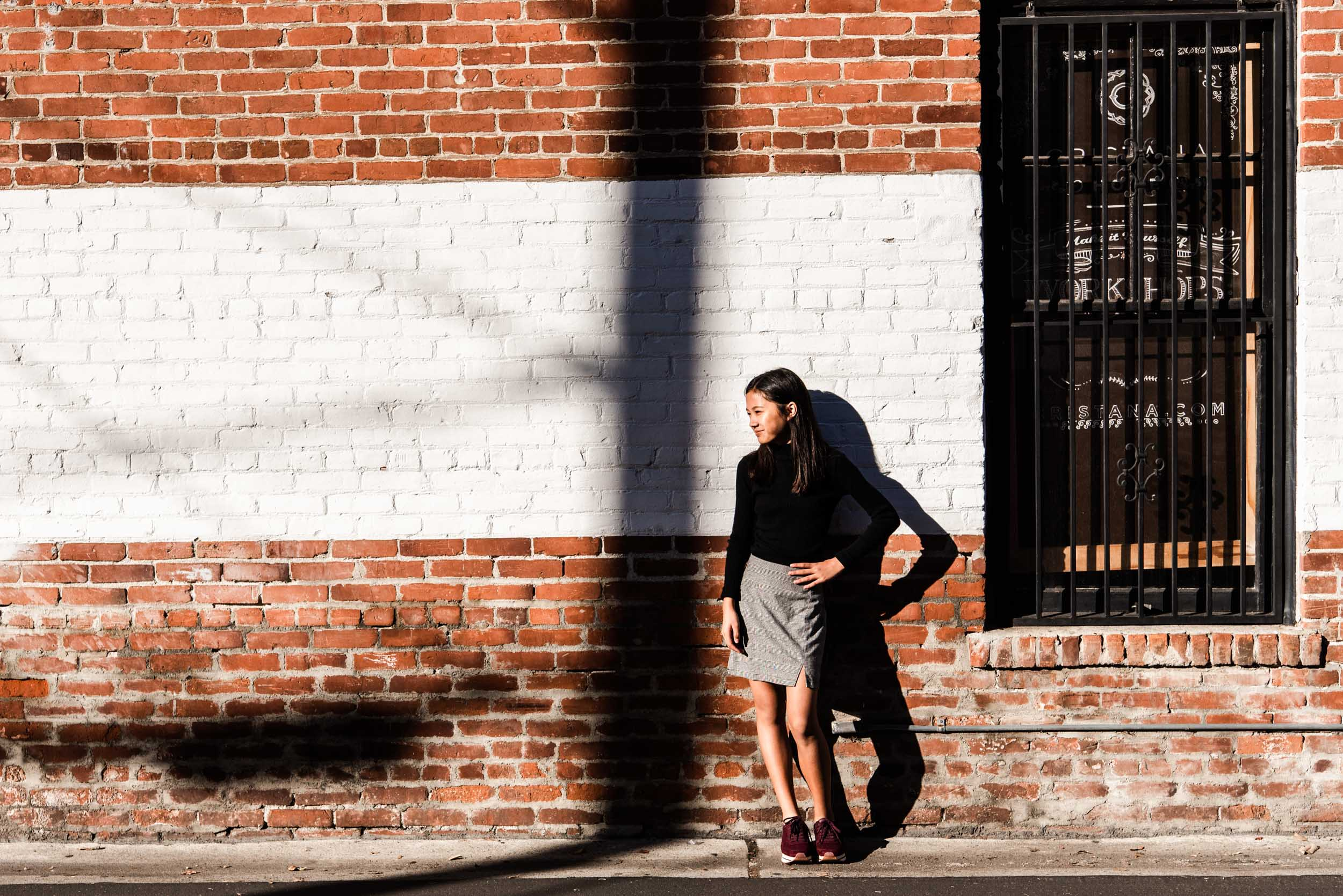 Lisa Hu Chen | young girl smiling while standing in front of a brick wall in Old Town Orange