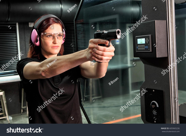 stock-photo-a-woman-firing-a-hand-gun-at-an-indoor-gun-range-605965226.jpg