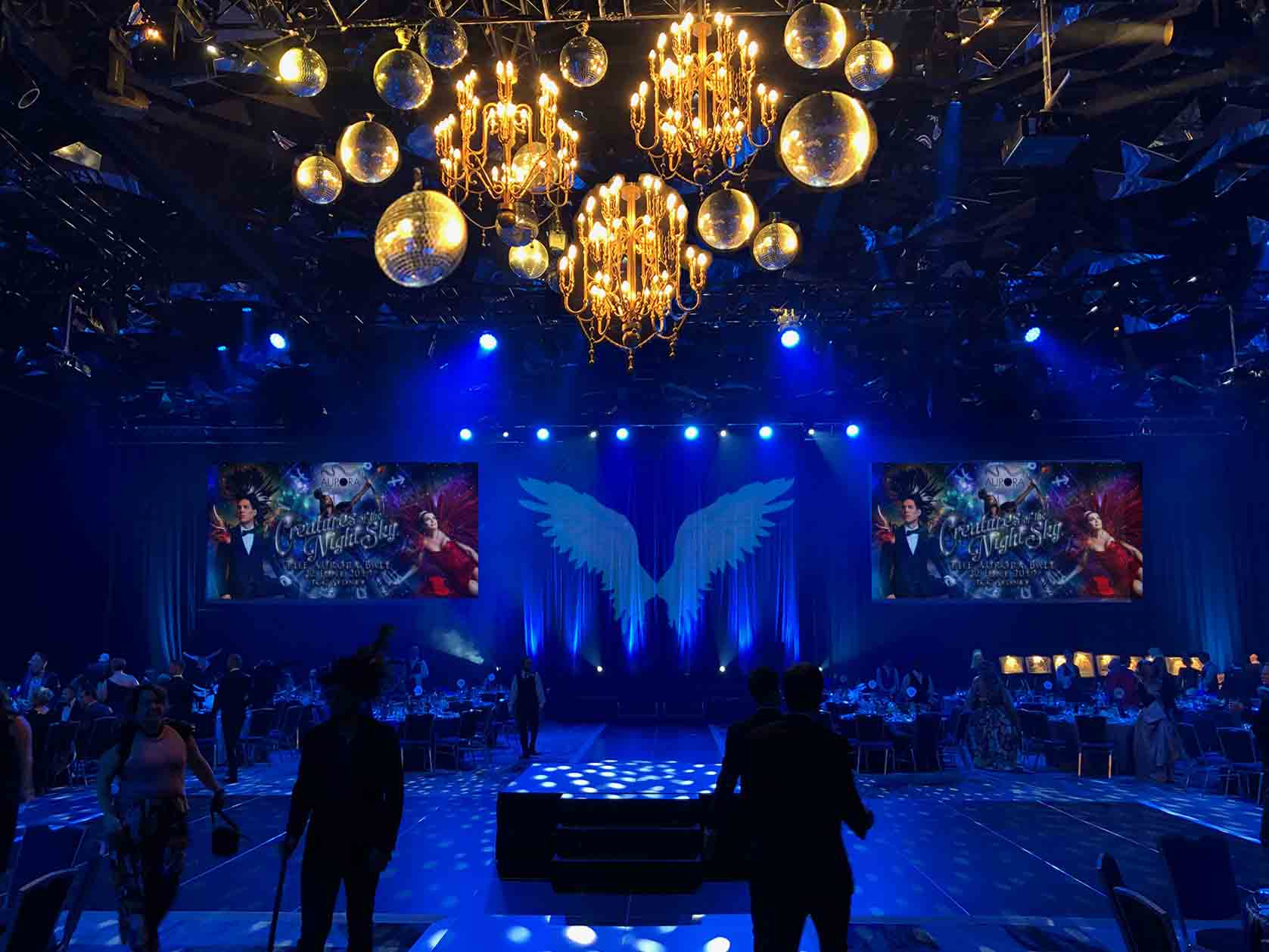 The design for the ball started as a blacked draped space with ascents of blue drapes highlighted with silver detail. This went through various design ideas landing on silver angel wings against tied blue drapes with blue drapes backing the main stage area. Central installation of gold chandeliers with various sized mirror balls to represent planets in the solar system over the dance floor.