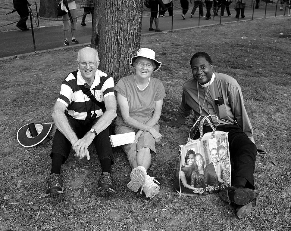 966px-Older_couple_sitting_under_a_tree_with_minister_in_purple_shirt_and_Obama_family_bag_-_50th_Anniversary_of_the_March_on_Washington_for_Jobs_and_Freedom.jpg