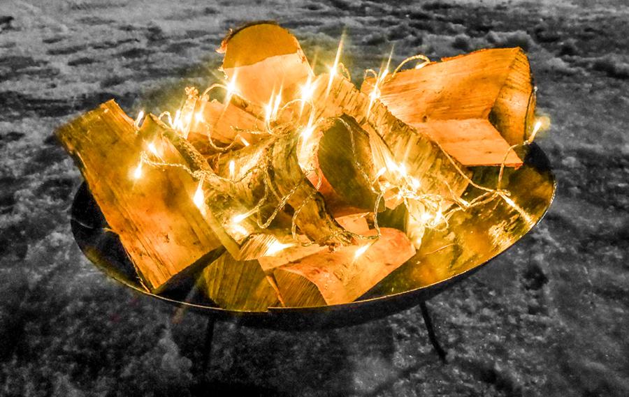 ryssfest brandsäkra eldfat med ved och LED slingor