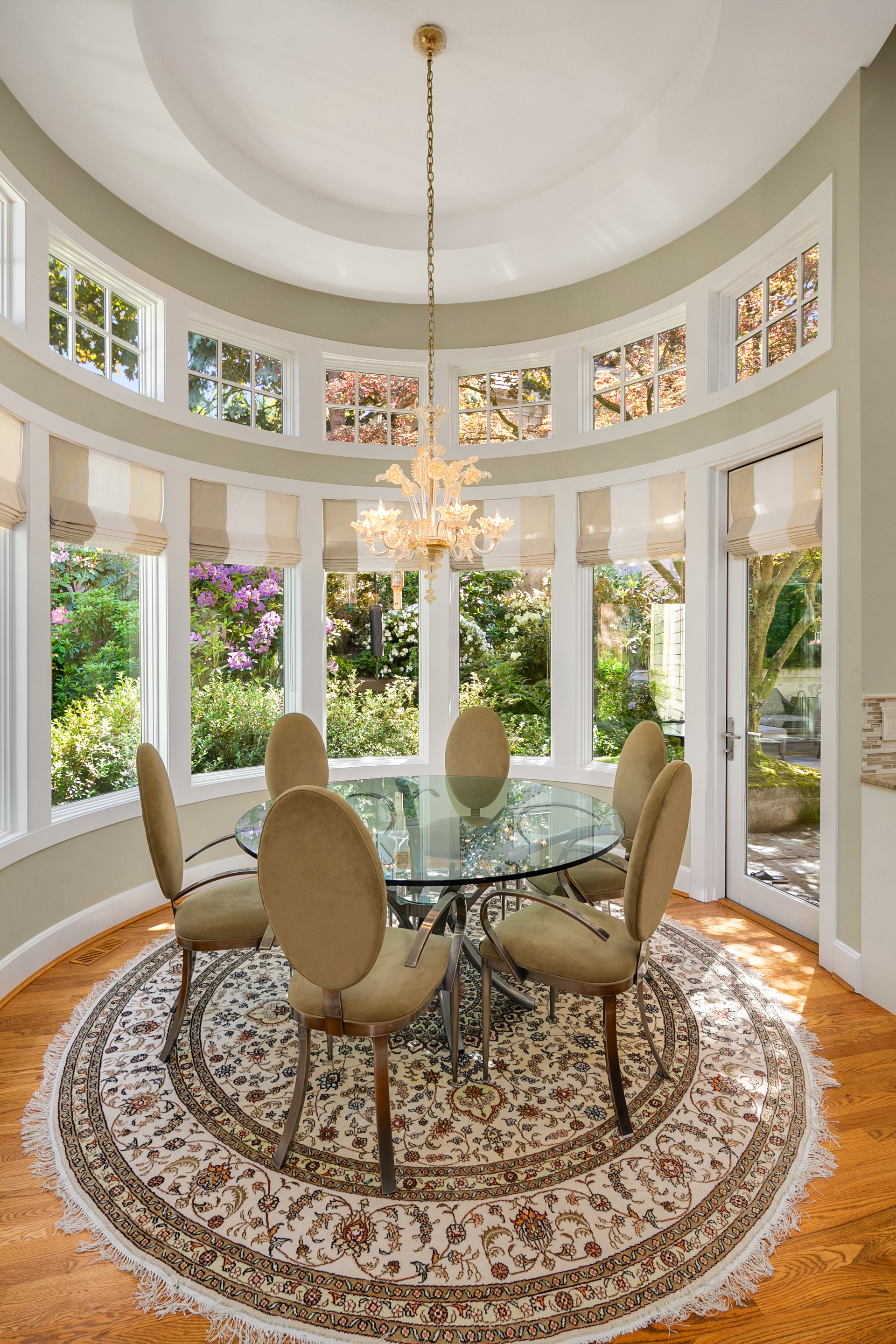 The circular breakfast nook offers a casual eating space with windows overlooking the gardens & access to the back patio.