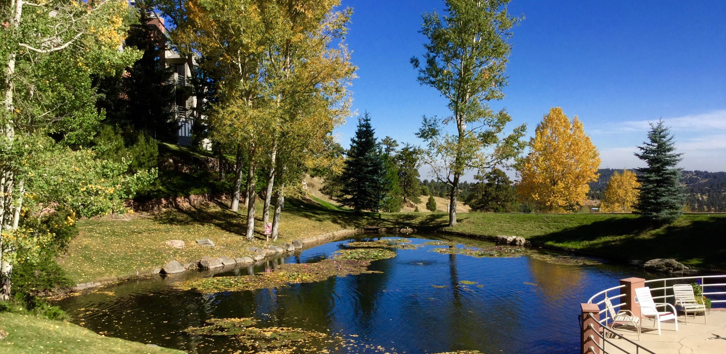 The Chimney Creek clubhouse and pool overlook a stream-fed pond at the center of the Community near Golden, Colorado