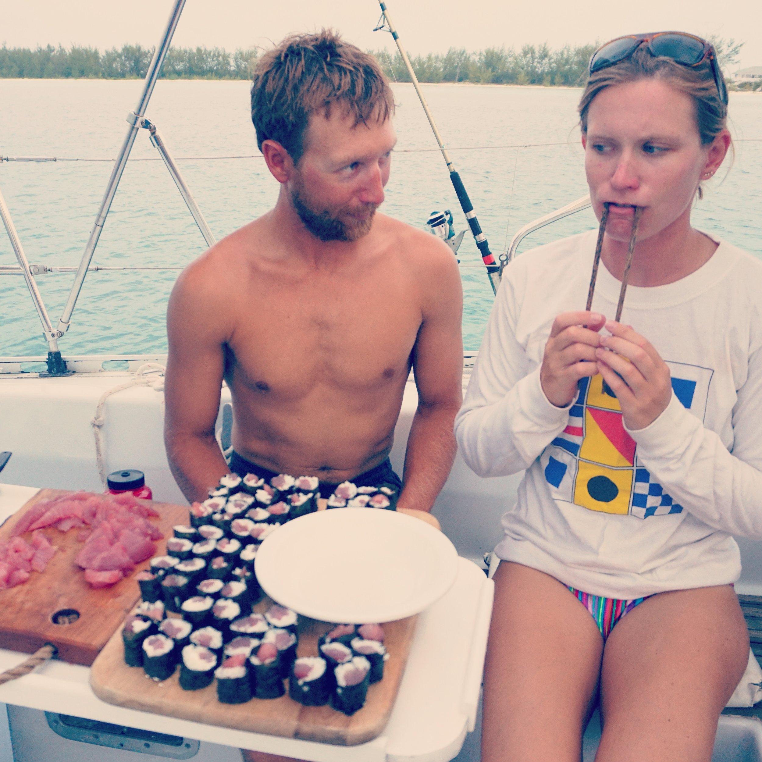 CHEF MOLLY AND CAPTAIN JOE EATING FRESH SUSHI SEAFOOD ABOARD MOJO SAILBOAT IN BAHAMAS