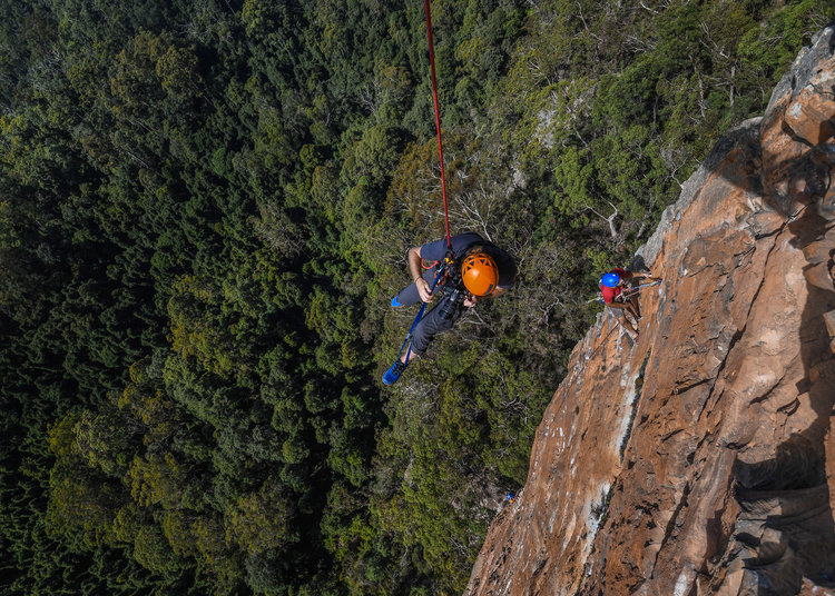 Adam setting up a shot, abseiling off a 150m cliff to get into position. Image: Jake Anderson