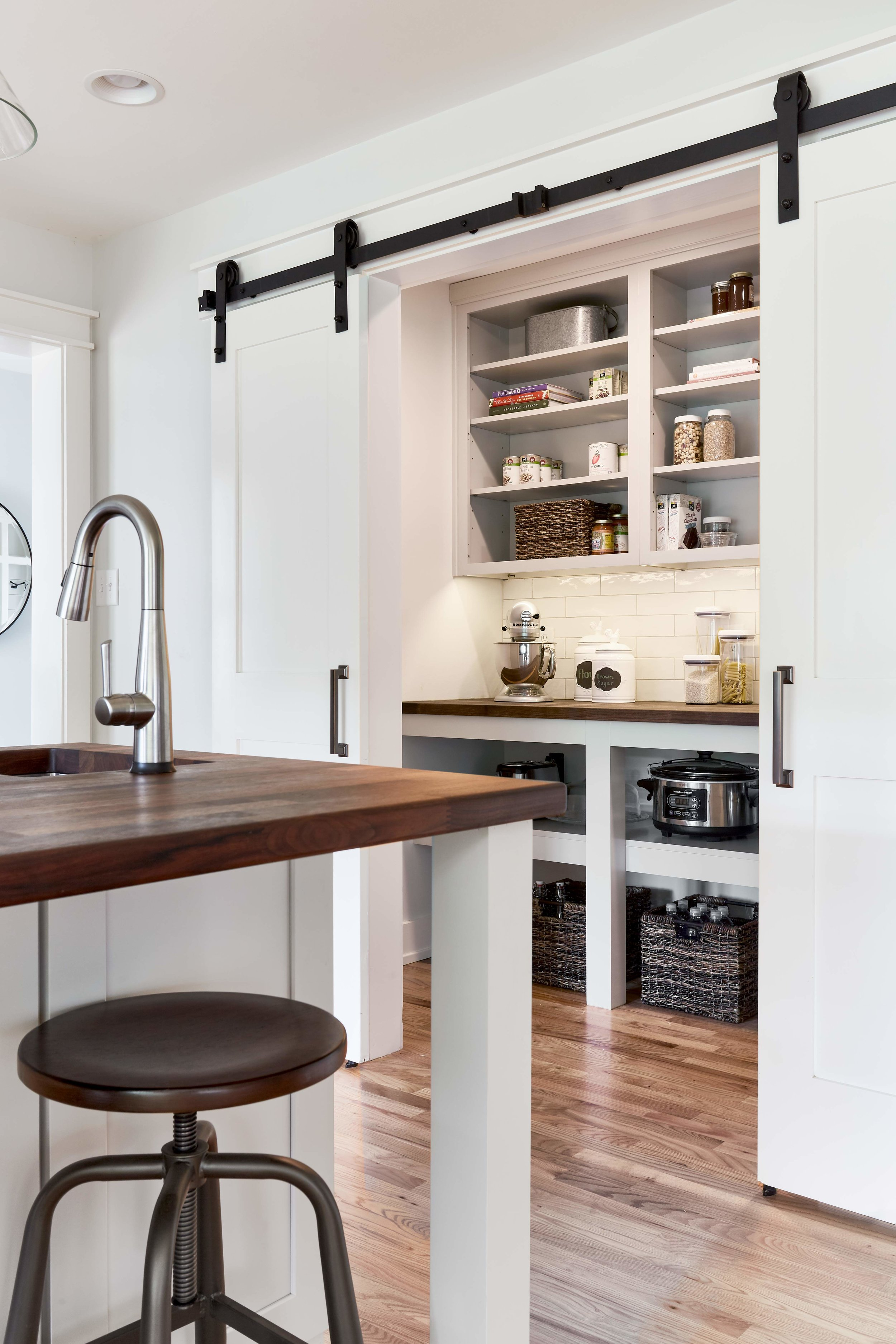 Renovated farmhouse kitchen featuring working pantry with sliding barn doors.