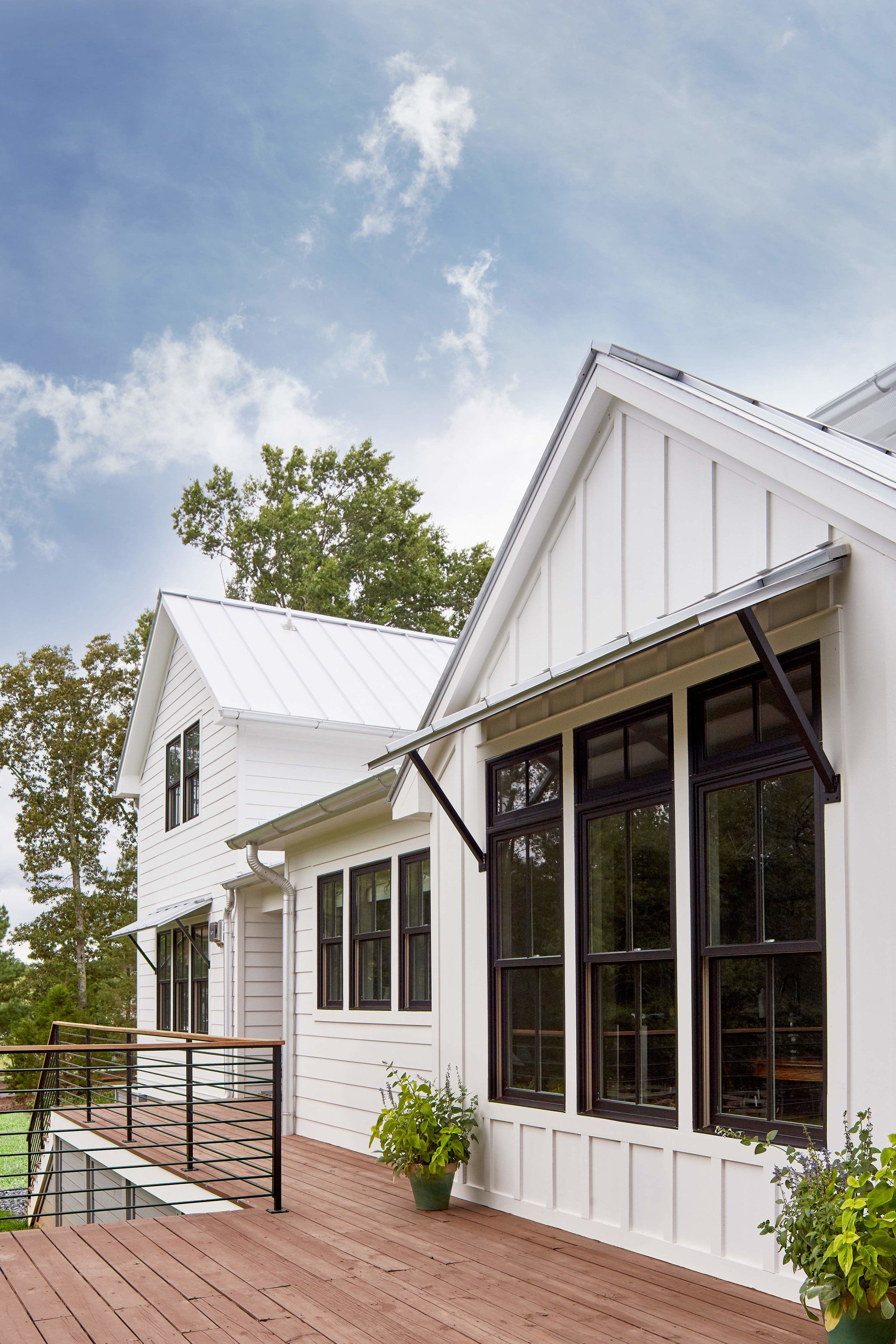 Rear exterior featuring new siding, new metal roof and custom awnings.