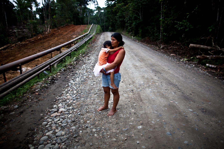 Ana vom Volk der Waorani und ihre Tochter laufen eine Ölstraße nahe ihrer Gemeinde in der Provinz Orleans, Ecuador, entlang.