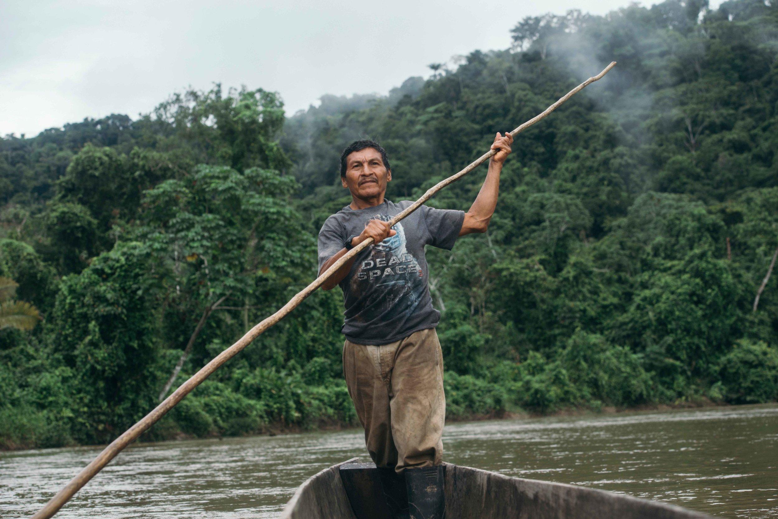 Ore in seinem Einbaumstammkanu beim Übersetzen zur anderen Flussseite.
