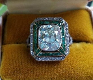 Old Mine Cut diamond set with emerald and diamond accents