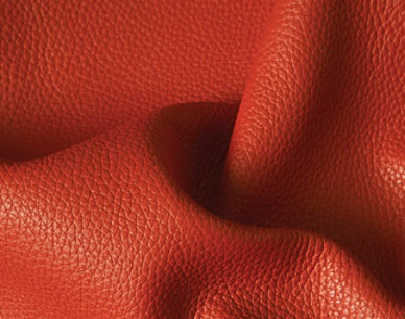 corrected grain leather  Leather which has been buffed or sanded to remove surface imperfections before having a surface coating applyed containing pigment . An artificial grain pattern is usually embossed into the surface .