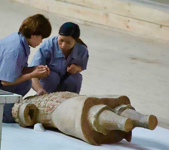 Painstaking work: two restorers piece together a soldier.