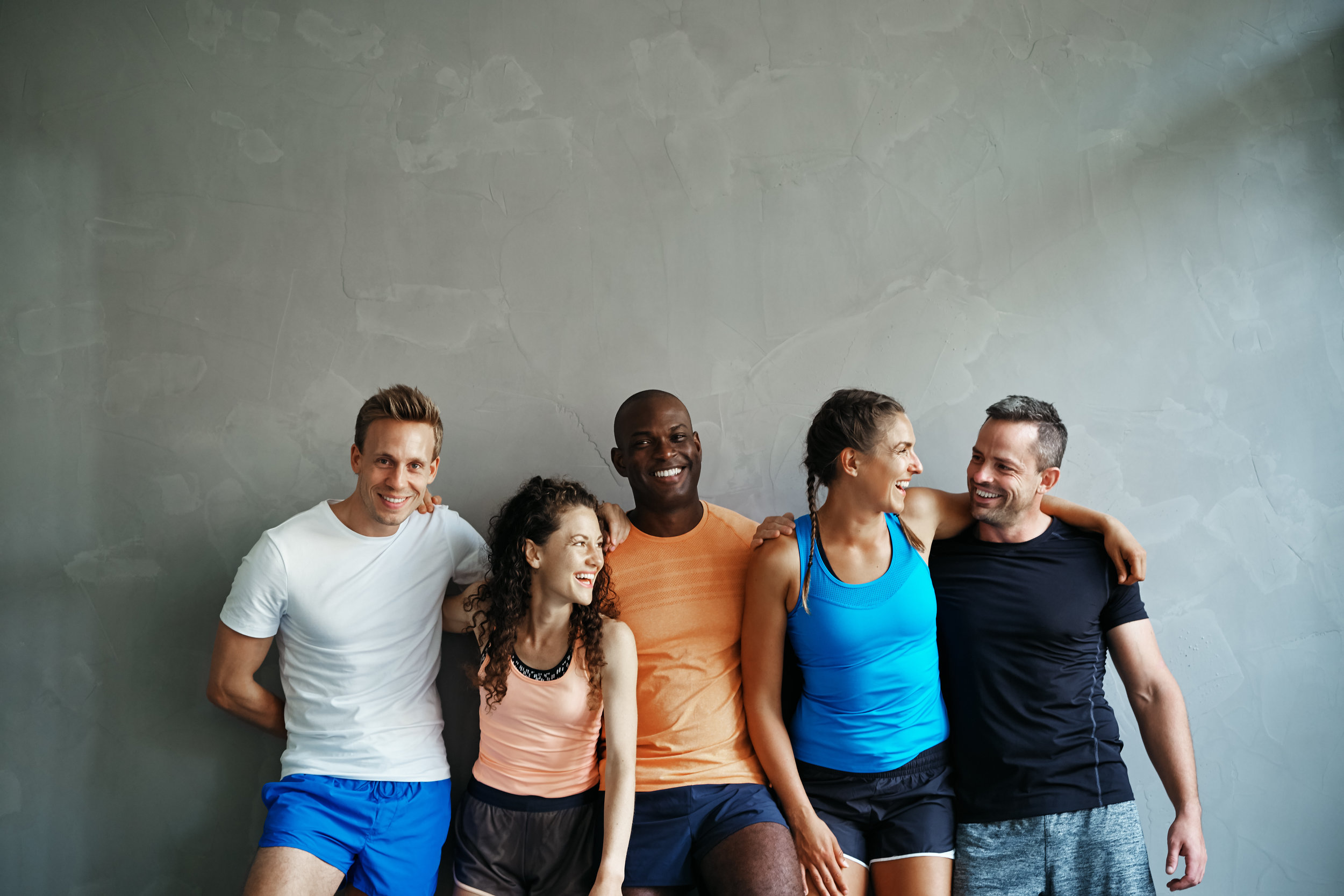 Diverse group of laughing friends standing together at the gym