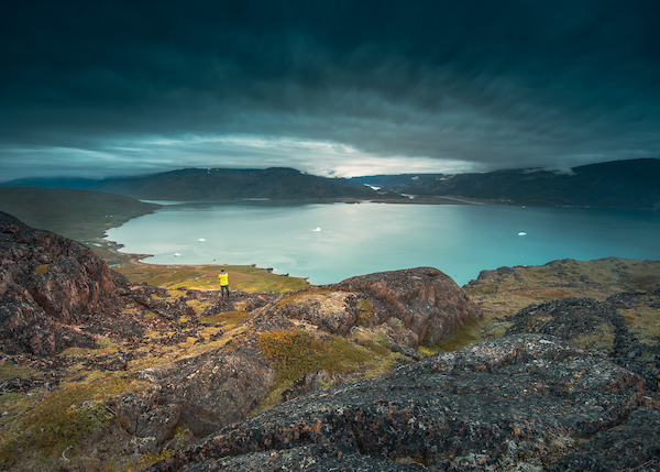 A lone traveller stands in Qassiarsuk and looks over Tunulliarfik Fjord toward Narsarsuaq, by Stacy William Head.jpg