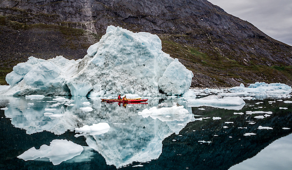 Two kayakers paddle around icebergs in Nuuk Fjord as a daytime adventure while staying at the Arctic Nomad Adventure Camp.jpg