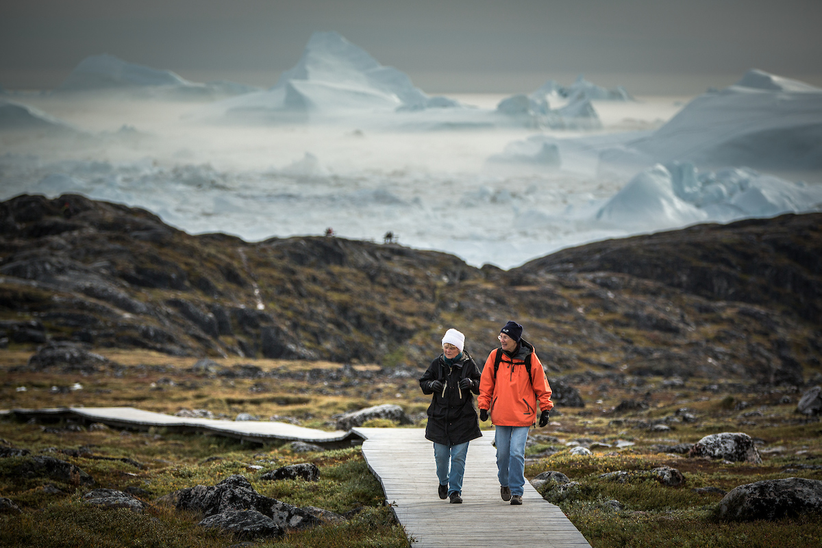 Two women on the boardwalk near Sermermiut with icebergs in the background in Ilulissat in Greenland.jpg