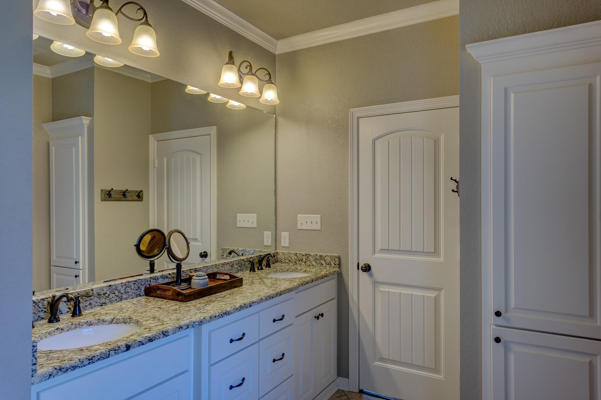 bathroom-remodeling-white-door-cabinets-sconce-fixtures.jpg