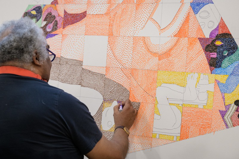 "Peter Williams, NA fills in the outlines he's drawn for a piece titled ""Once We Built Pyramids,"" referring to the ancient Nubian Dynasty in Africa. He uses thousands of brightly colored dots, creating a different look from the traditional pointillist painting technique pioneered by 19th century artists such as Georges Seurat."