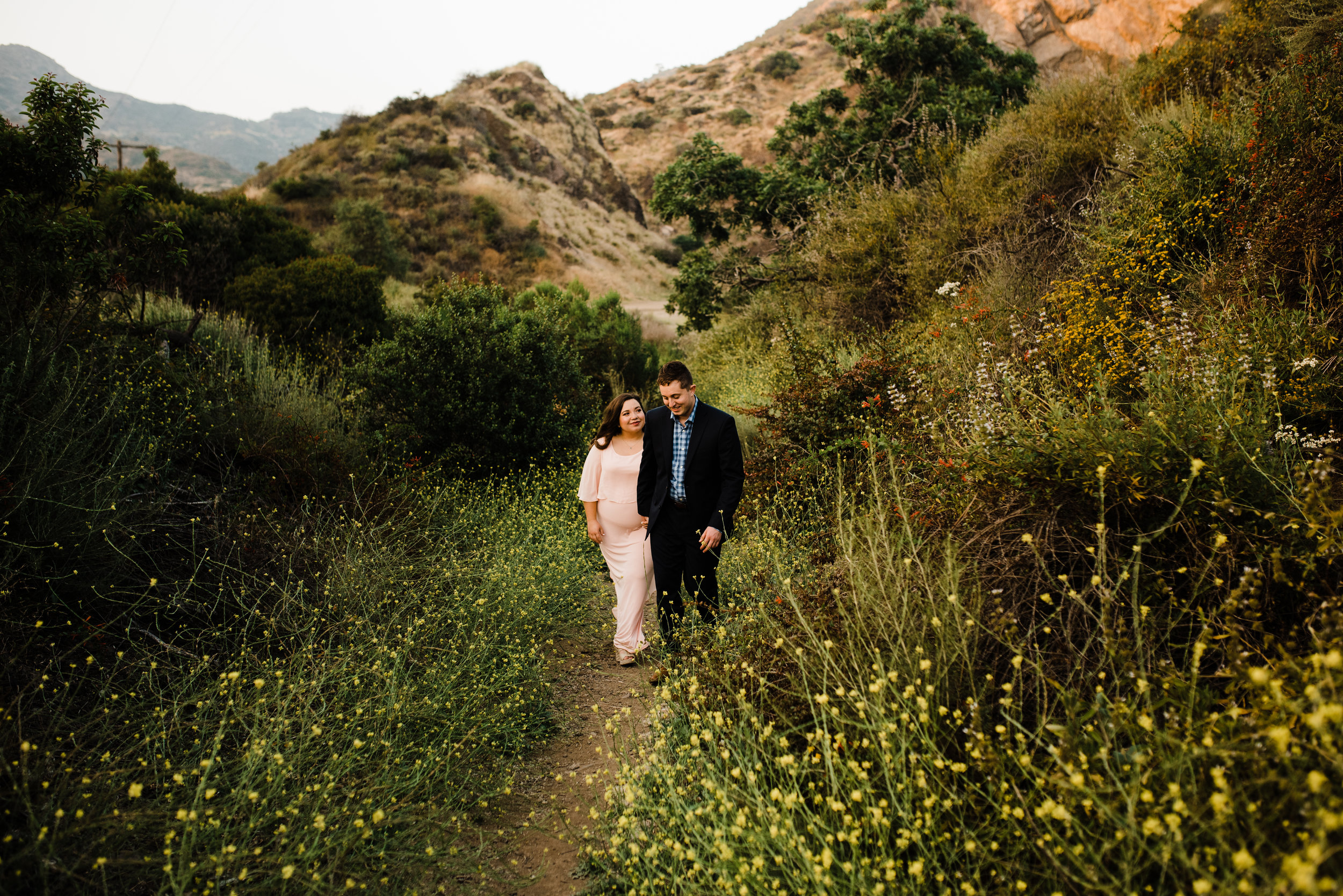 Couple walking through wildflowers and mountains in Los Angeles, California for their adventurous engagement shoot