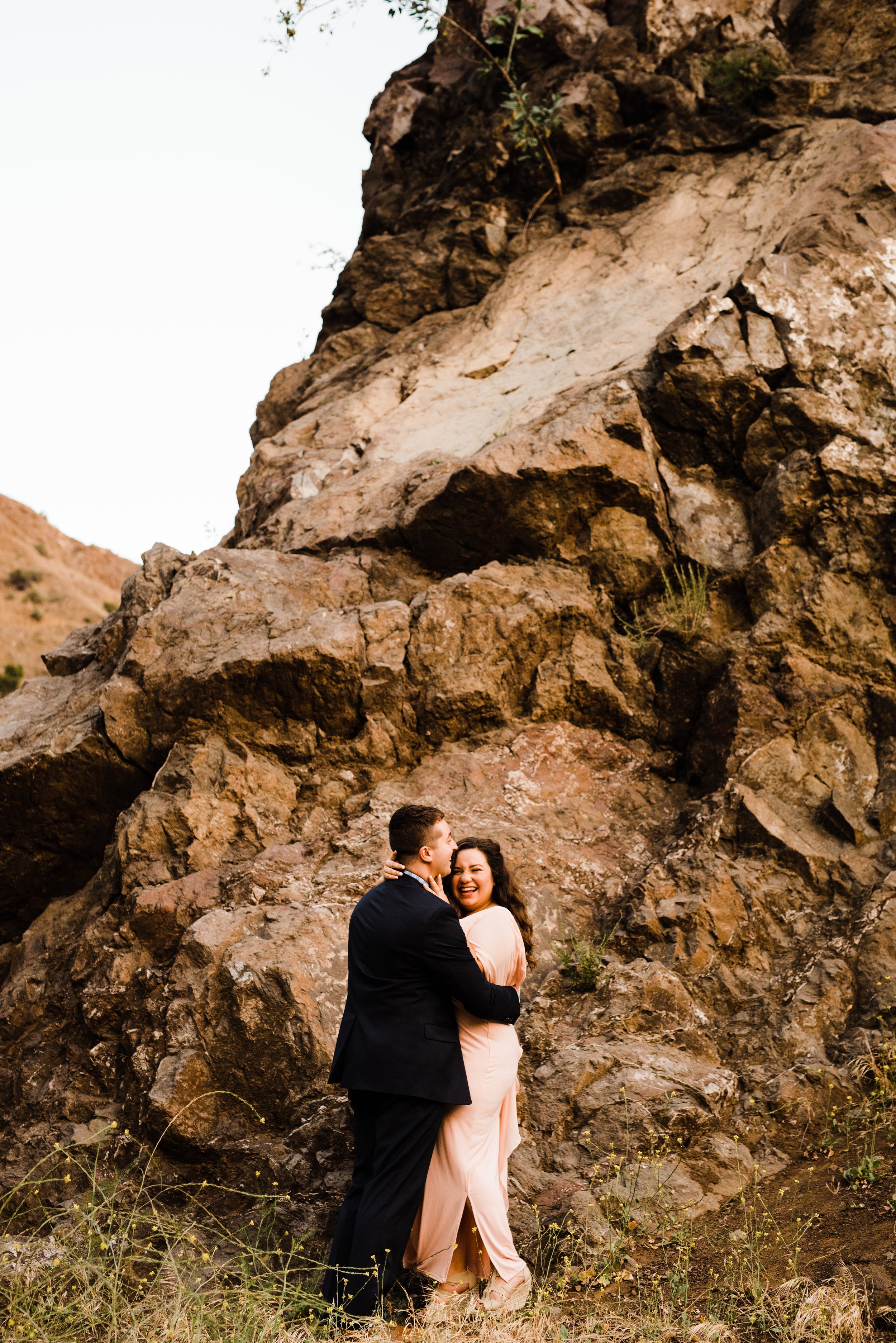 Couple laughing at Bronson Canyon in LA at their adventurous engagement session