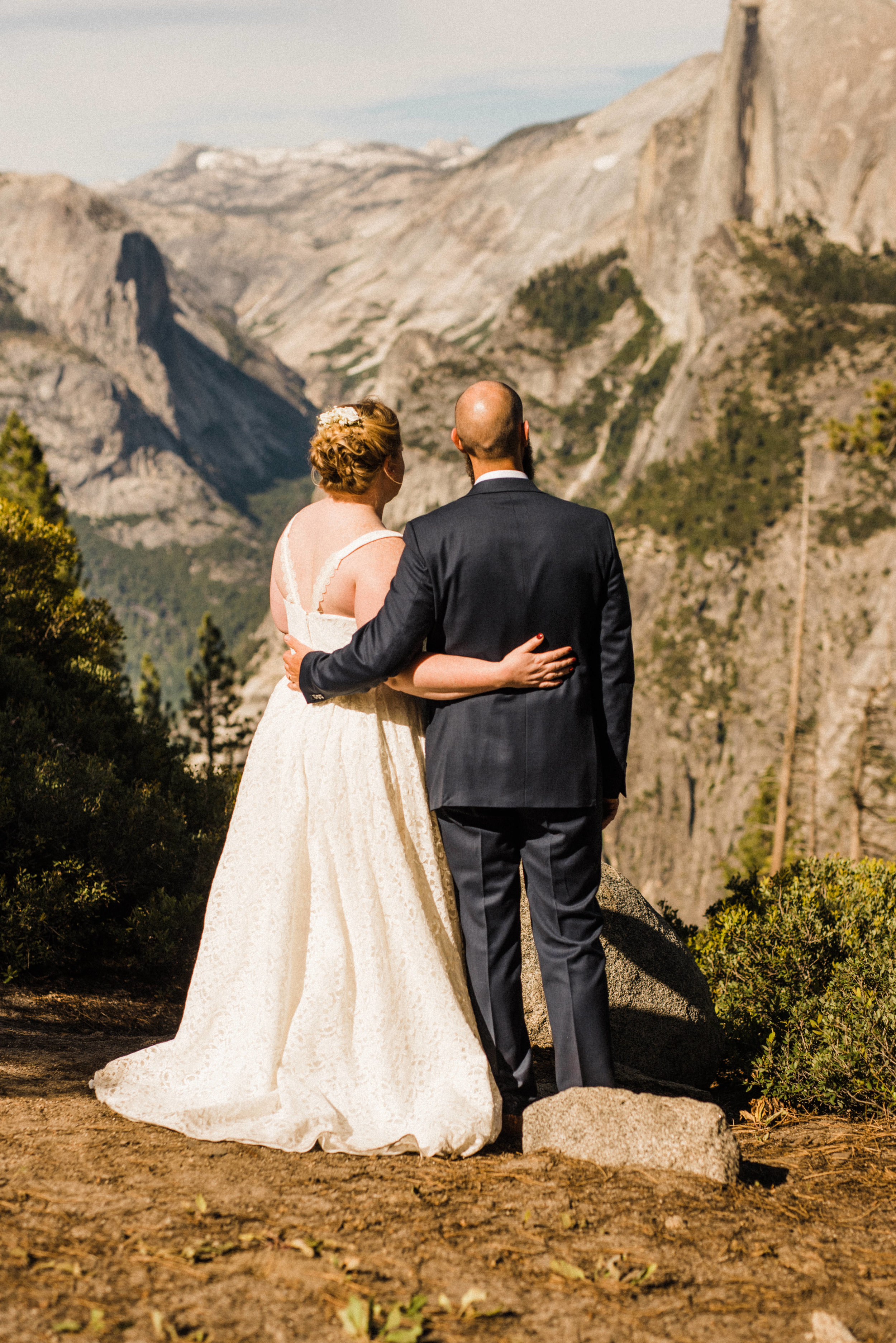 Bride and Groom on the cliff at Glacier Point in Yosemite, facing Half Dome and Yosemite Falls
