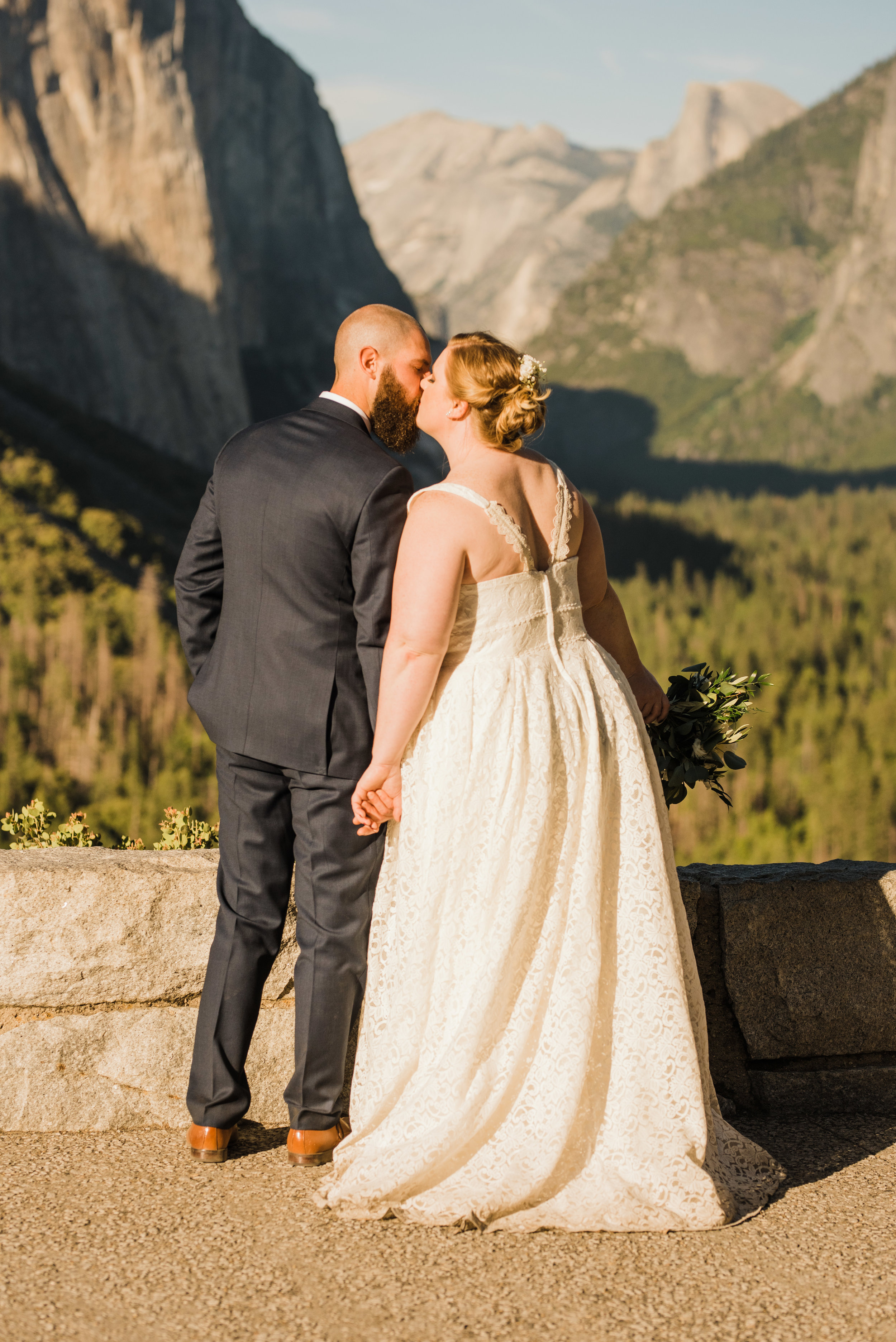 Bride and groom kiss in front of El Capitan and Half Dome in Yosemite National Park in the same spot that Ansel Adam once photographed: Tunnel View