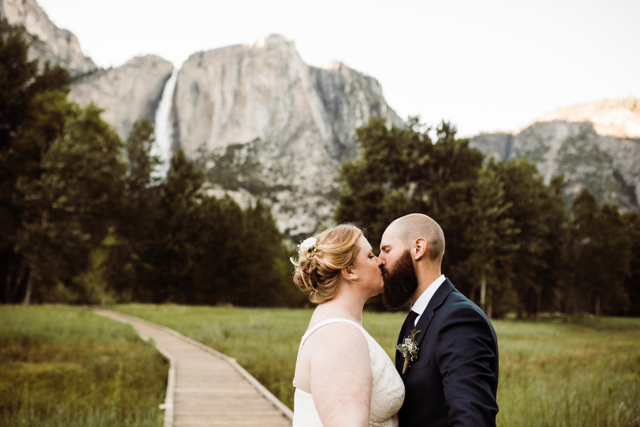Elopement Couple Kissing beneath Yosemite Falls in Yosemite National Park