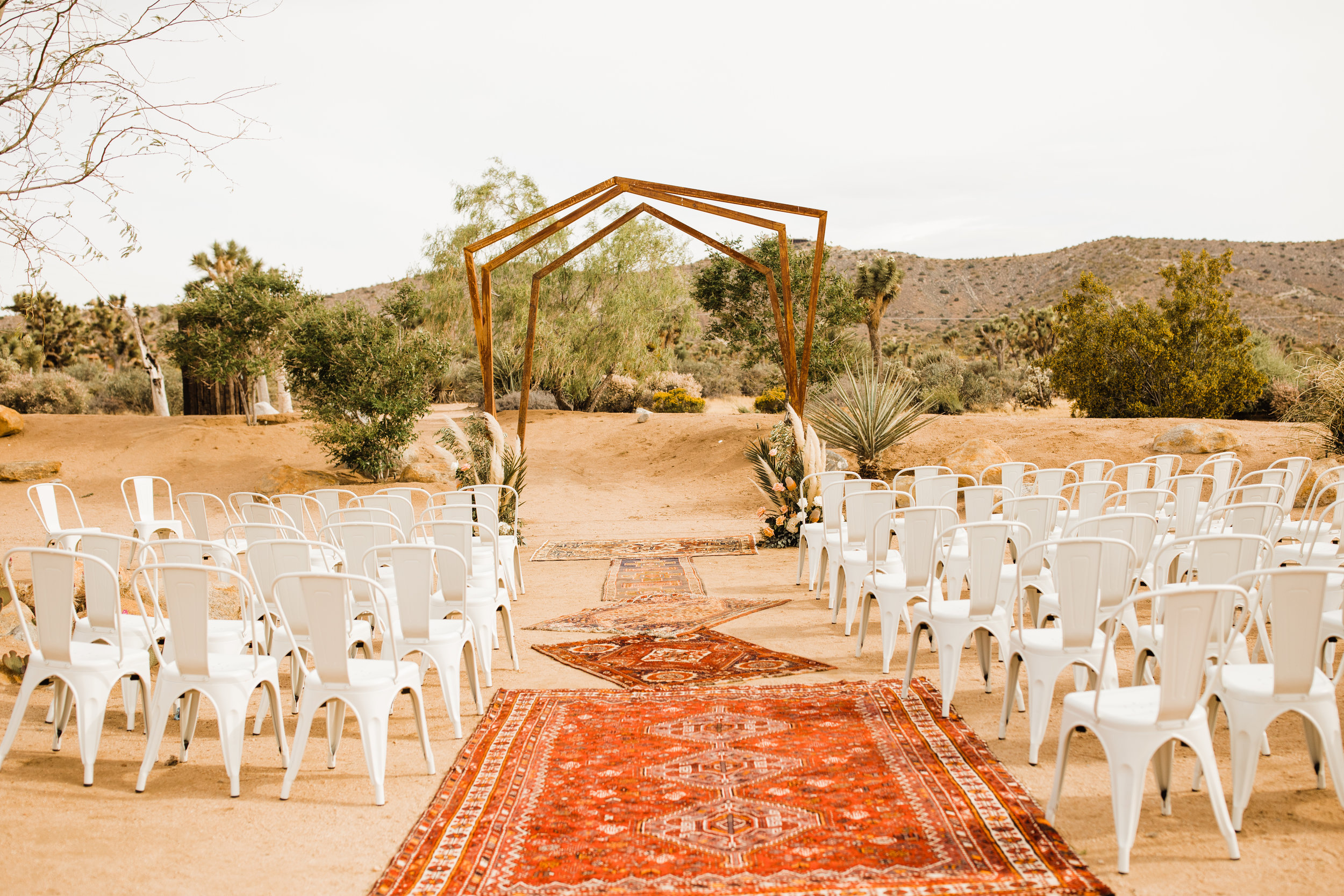 Tumbleweed Sanctuary and Garden Wedding Venue with Bohemian Distressed Rugs in Red and Orange Desert Color Scheme