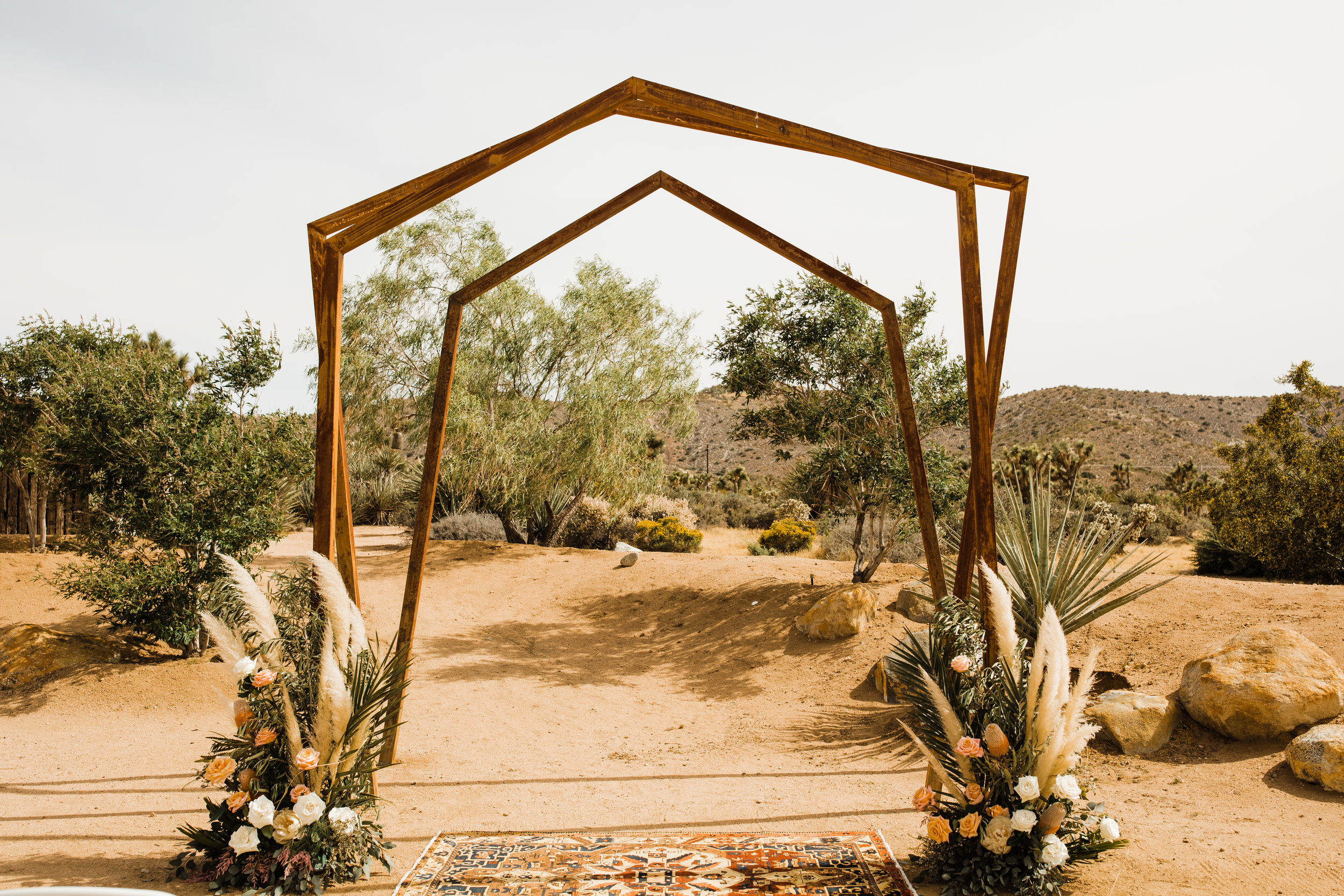 Metal arch at Tumbleweed Sanctuary and Garden Ceremony Site with florals from Pinyon Pine Floral Design. I love the dried pampas grass against the greenery and the pink roses!