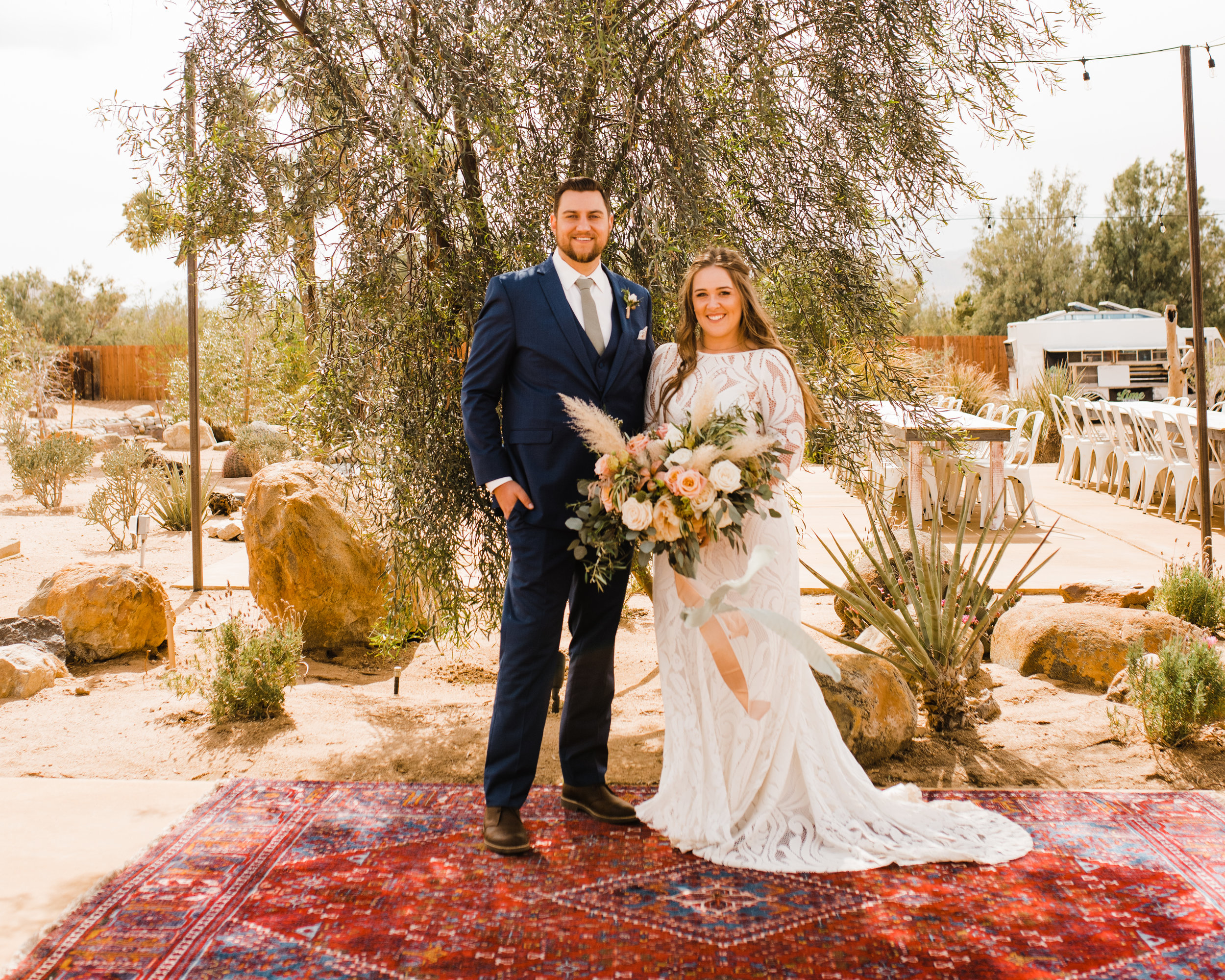Bride and Groom pose for a portrait before the ceremony at Tumbleweed Sanctuary in Joshua Tree, California with desert-inspired boho florals