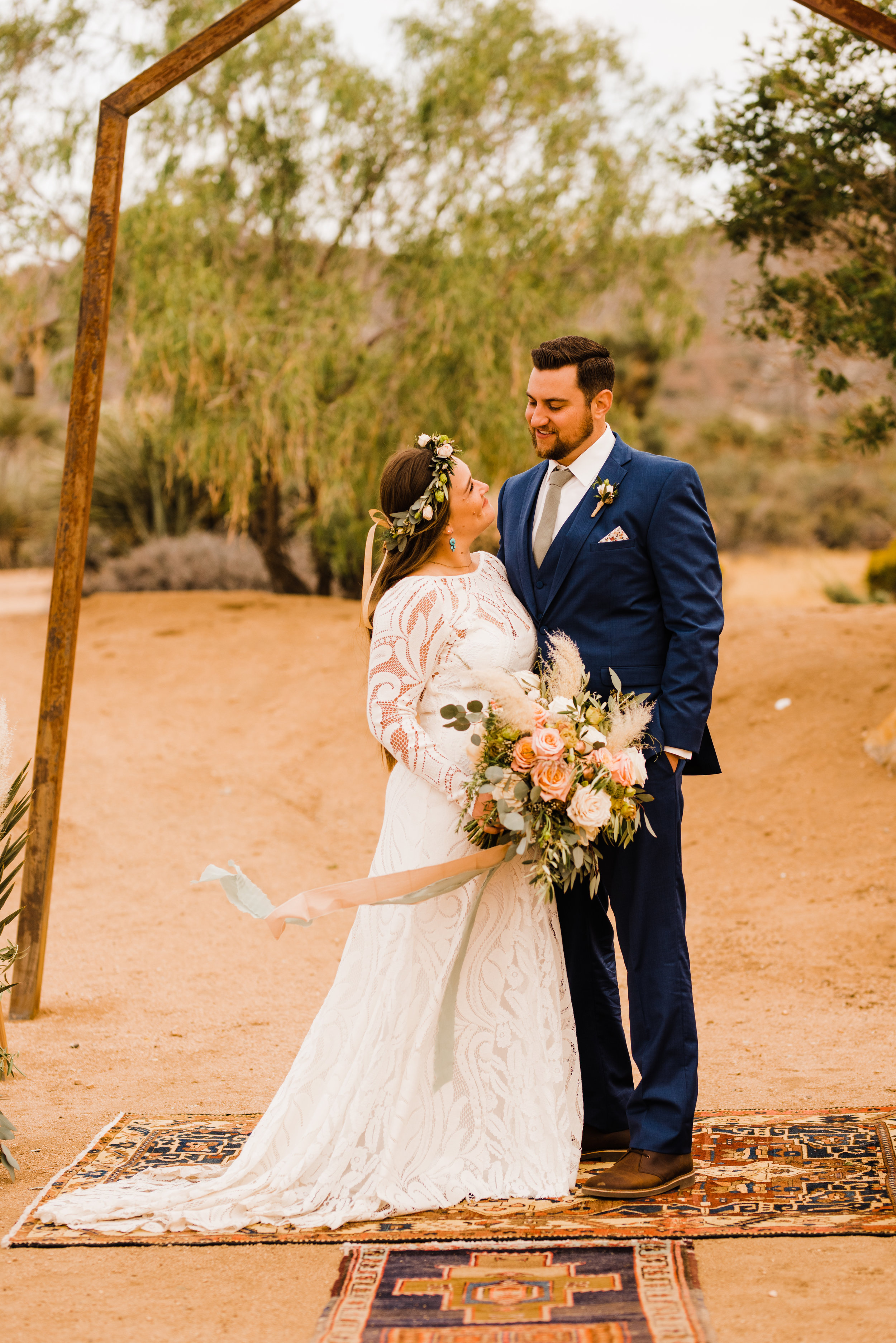 Bride in Lovers Society North Gown with White and Green Flower Crown. Groom in Friar Tux blue suit and pink tie.