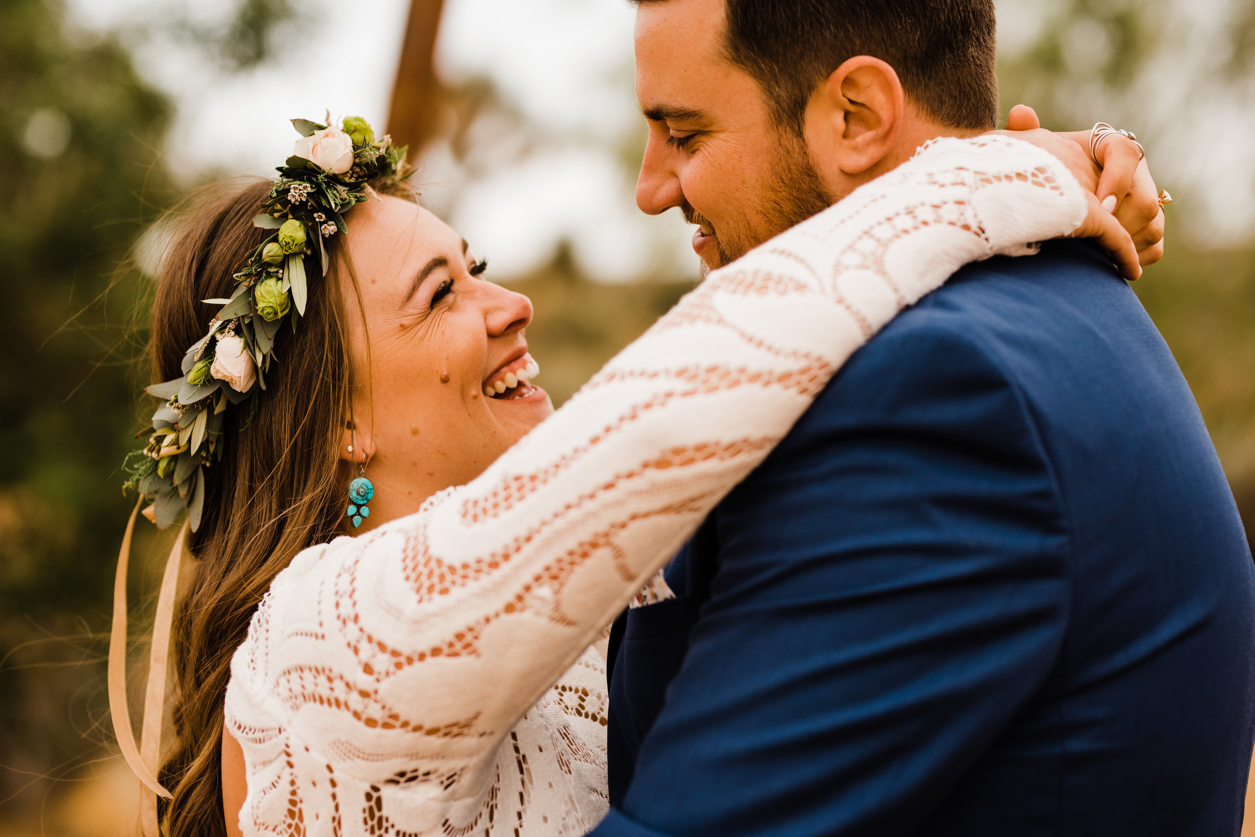 Bride laughing with white and green Hawaiian flower crown.