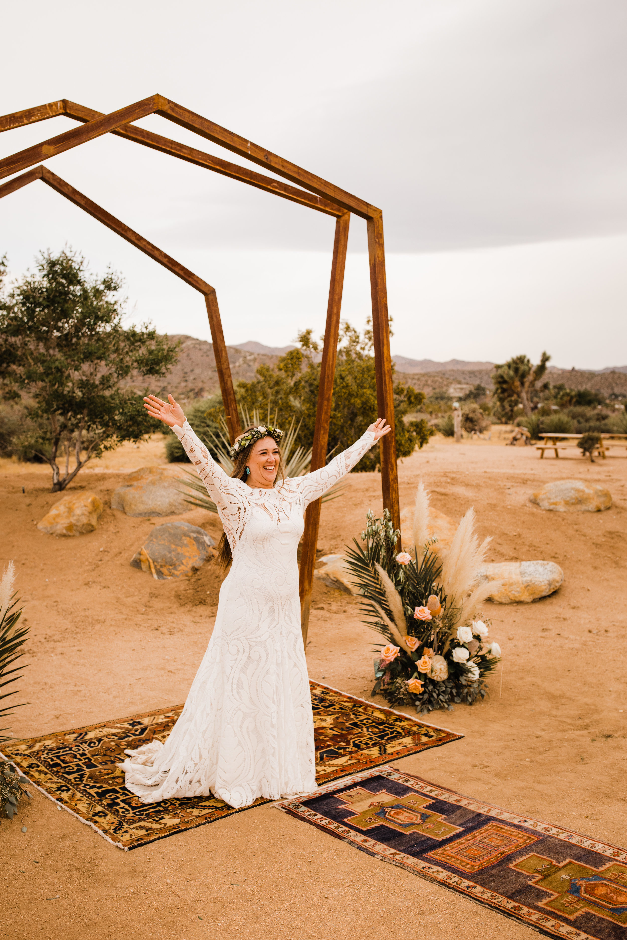 Excited bride beneath metal arch at Tumbleweed Sanctuary and Garden