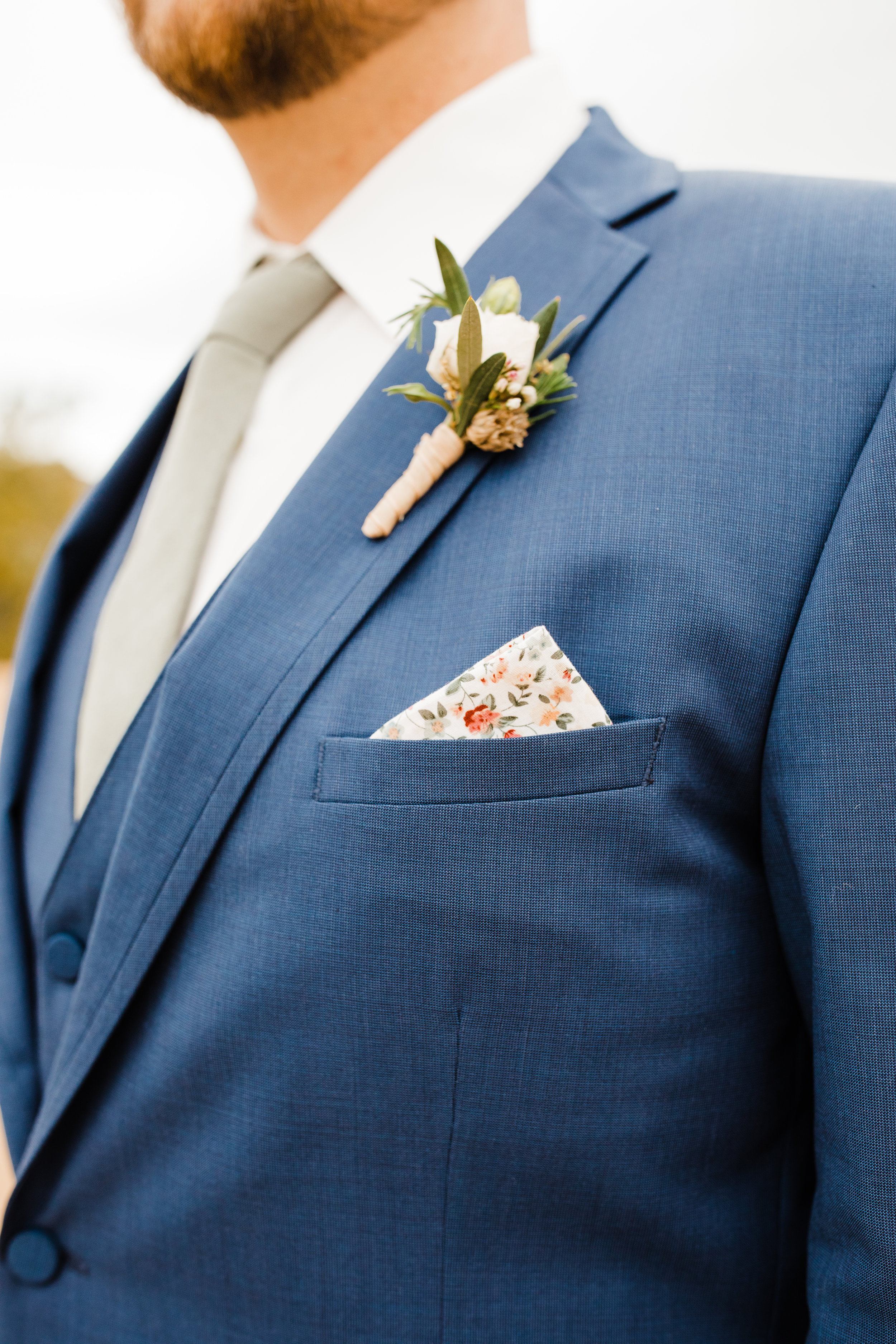 Groom's Floral Pocket Square Detail and Boutonniere. Blue Suit by Friar Tux and flowers by Pinyon Pine Floral Design.