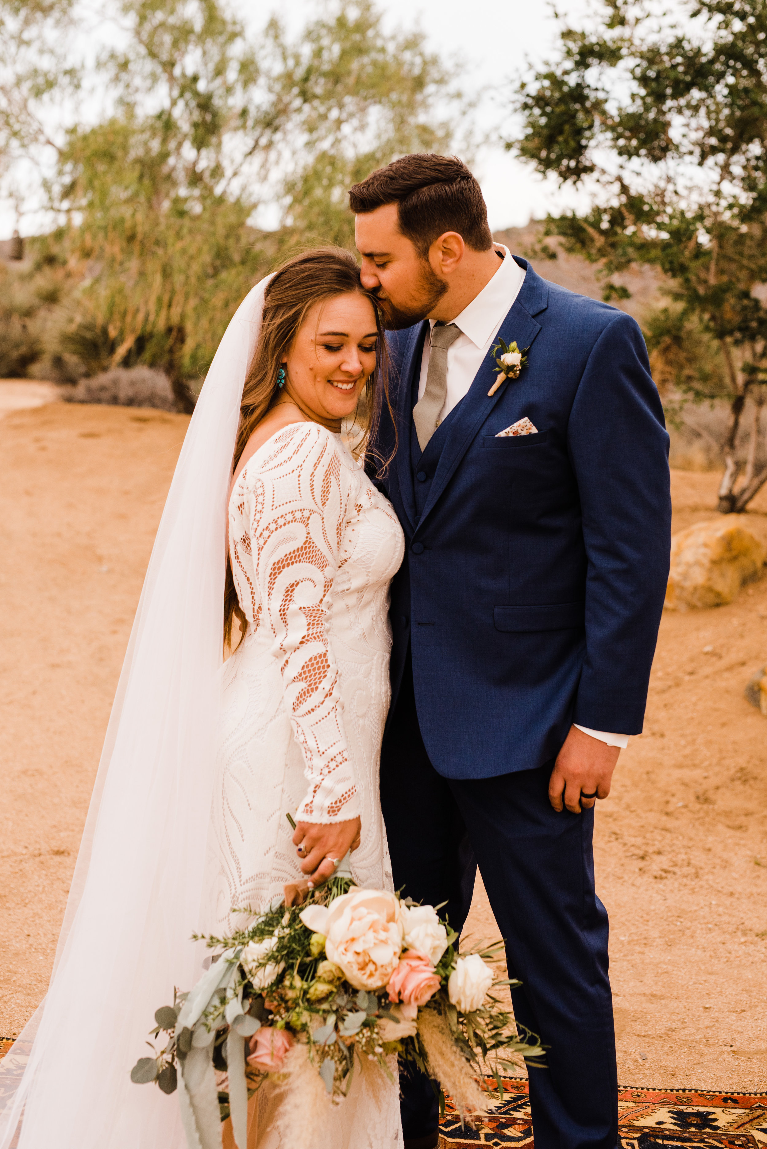 groom gives forehead kisses to bride at tumbleweed sanctuary wedding