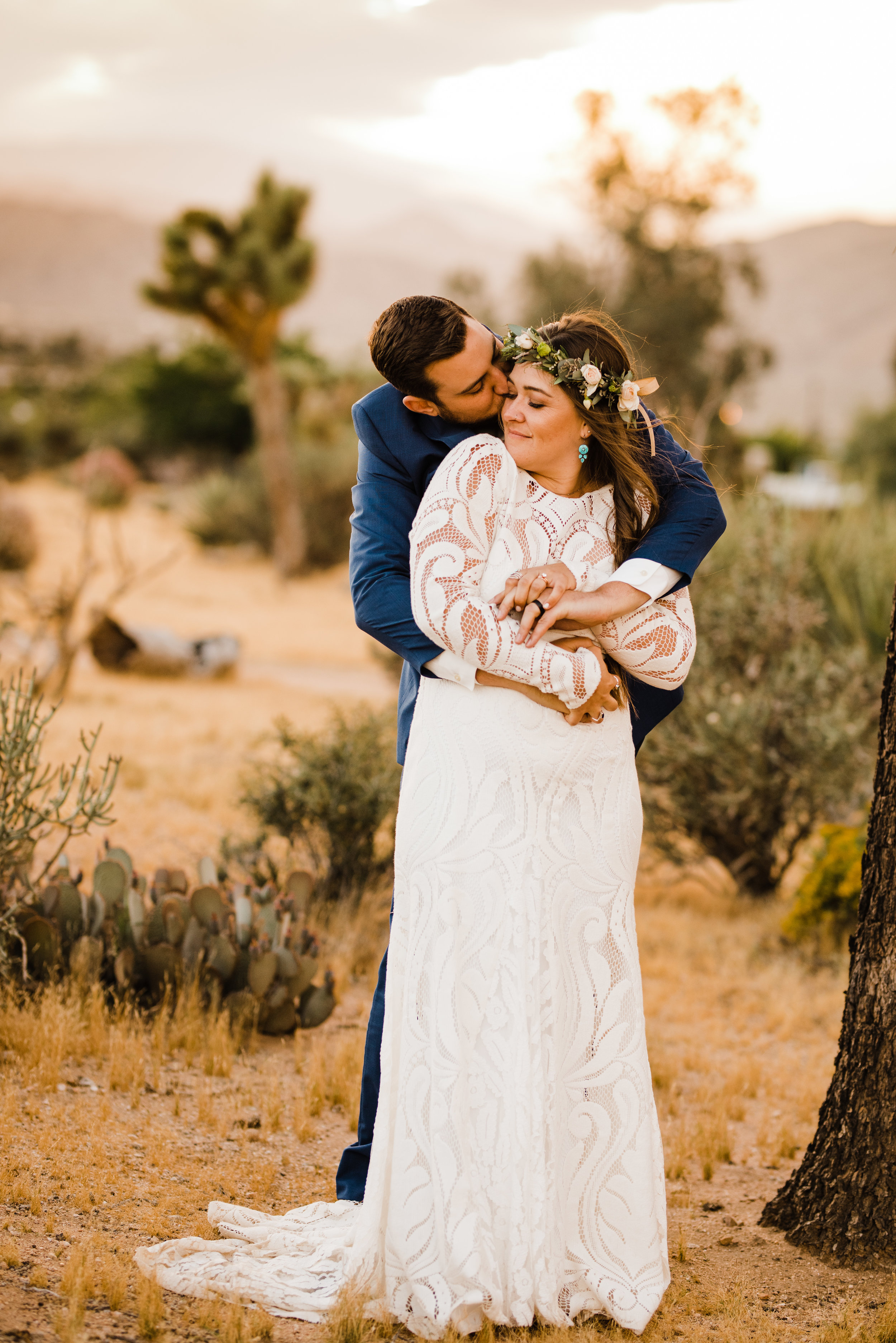golden hour photo of bride and groom at tumbleweed sanctuary hugging - bride's dress by lovers society and groom wearing a suit by friar tux