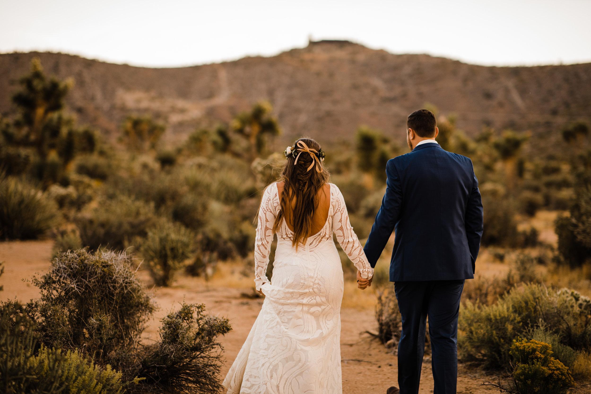 bride and groom walking in joshua tree desert behind tumbleweed wedding venue