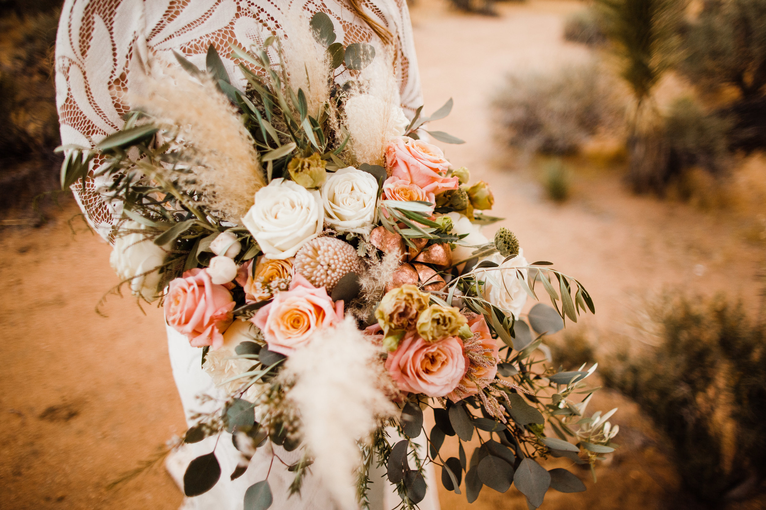 bridal bouquet of dried pampas grass, feathery elements and a copper rose mixed in with white and pink flowers
