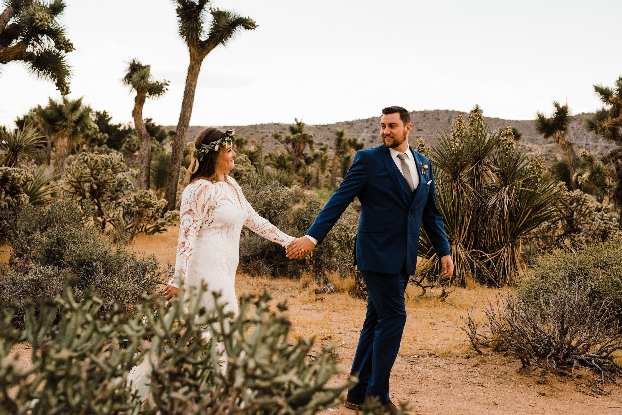 bride and groom walking through joshua tree