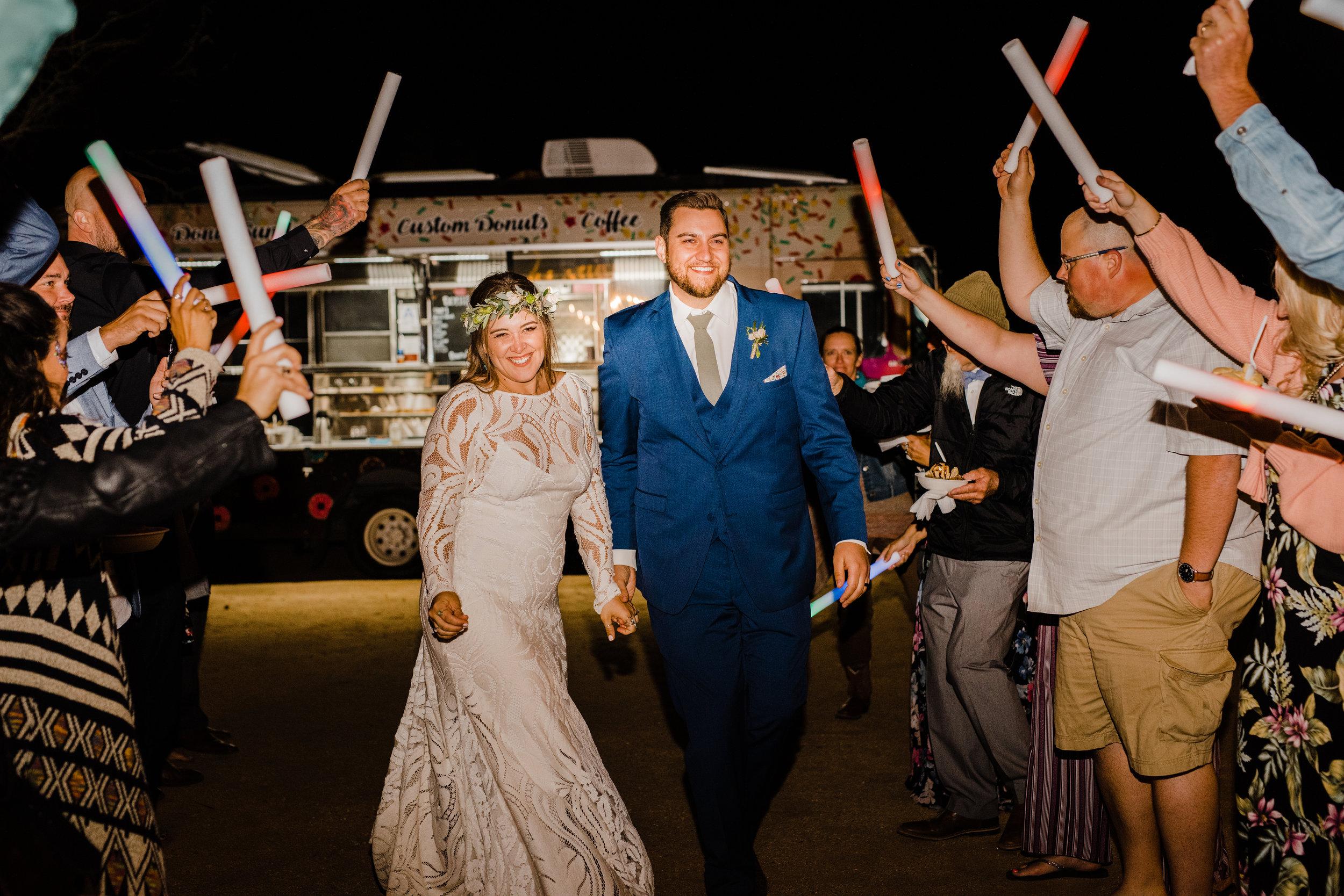 Bride and groom exit with glow sticks at Joshua Tree venue Tumbleweed Sanctuary