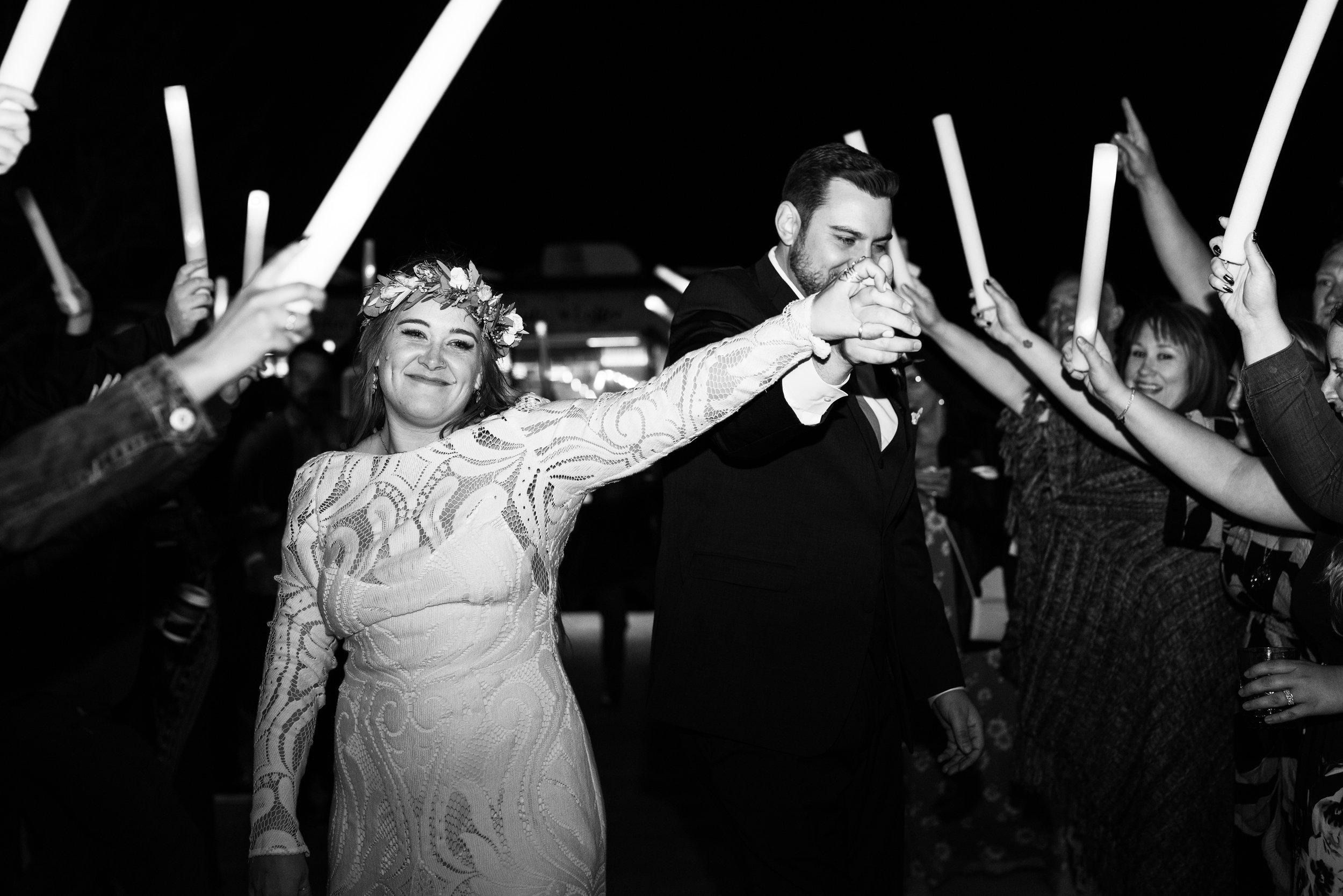 happy bride during glowstick wedding reception exit