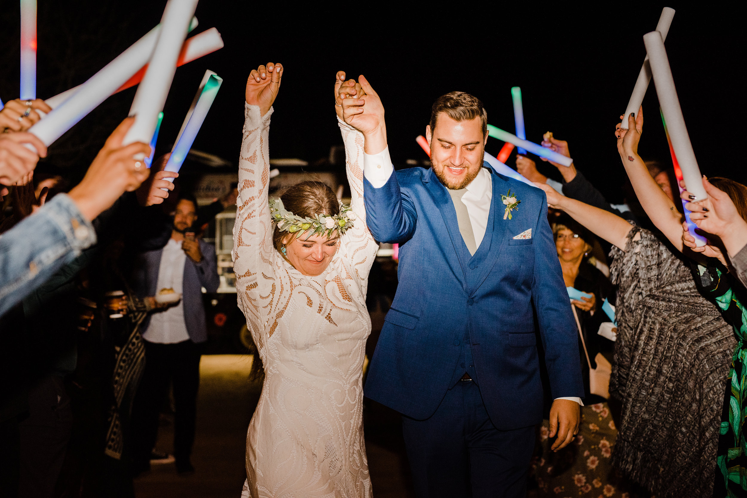 Bride cheers during glowstick wedding reception exit