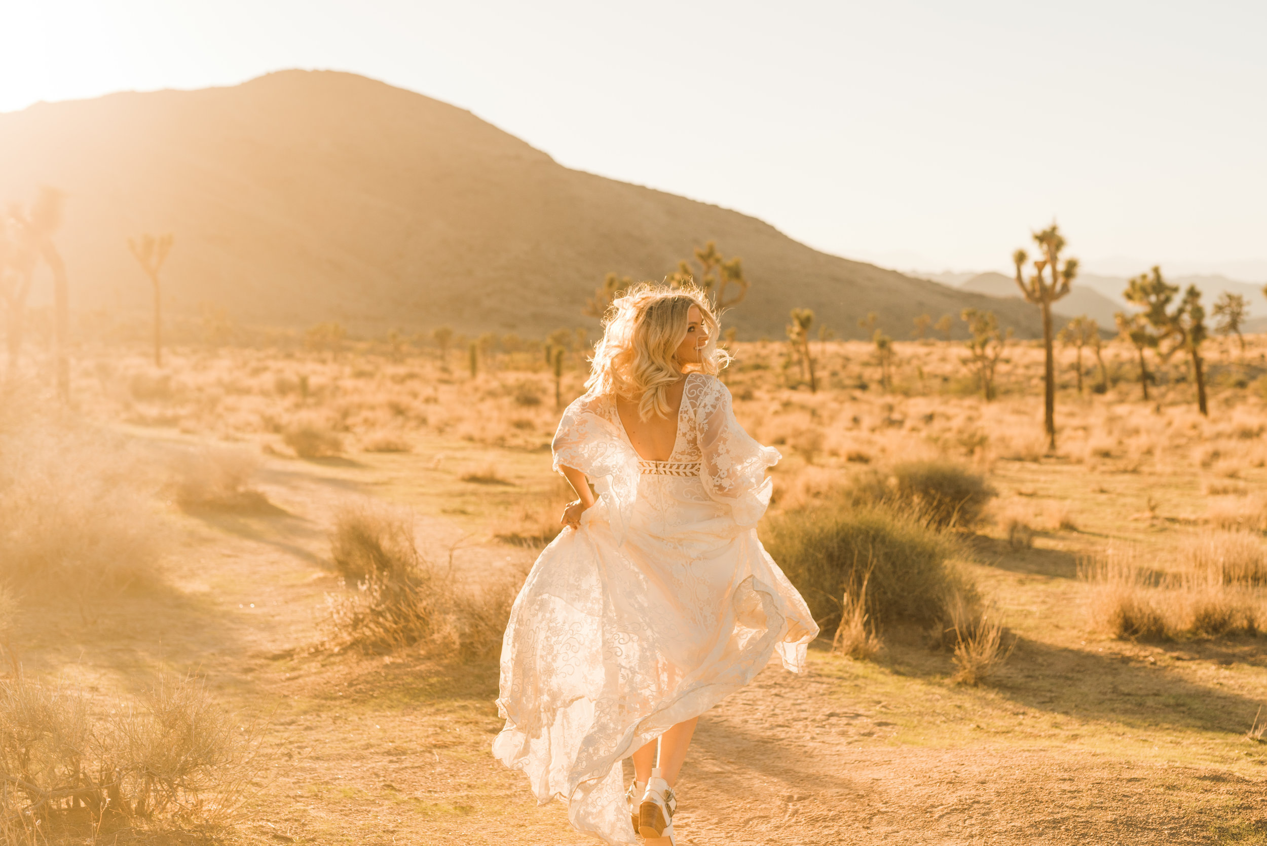 Bride in ankle boots and Rue De Seine runs during golden hour in Joshua Tree National Park in Rue De Seine boho lace dress