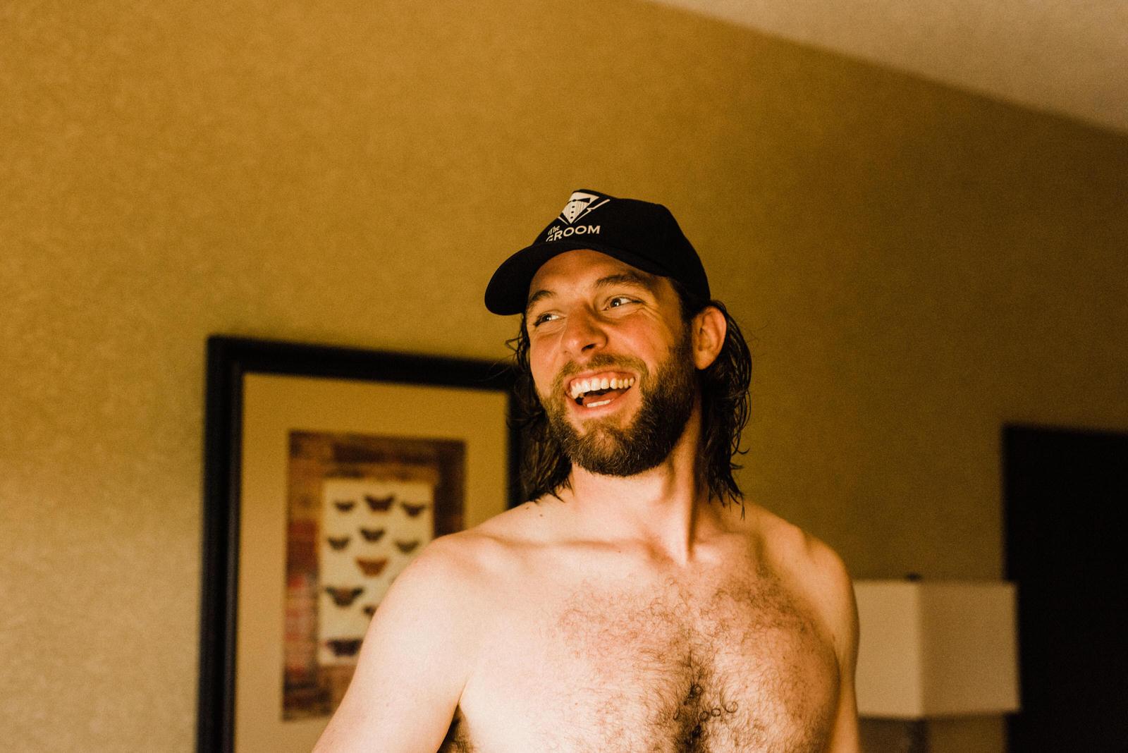 "Groom wearing custom ""Groom"" baseball hat while getting ready in DoubleTree hotel before Roswell River Landing Wedding"