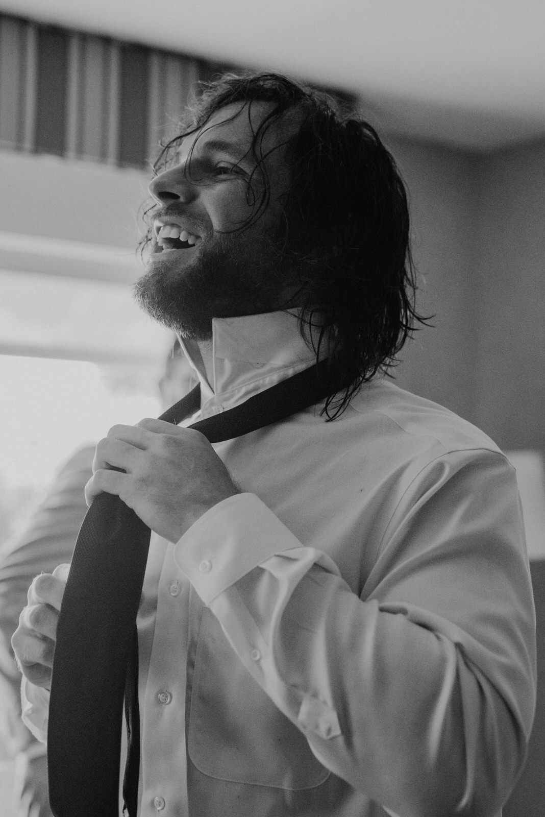 Groom laughs while getting ready before Roswell River Landing Wedding