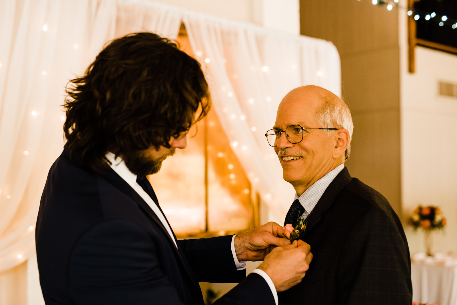 Groom pins boutonniere on dad