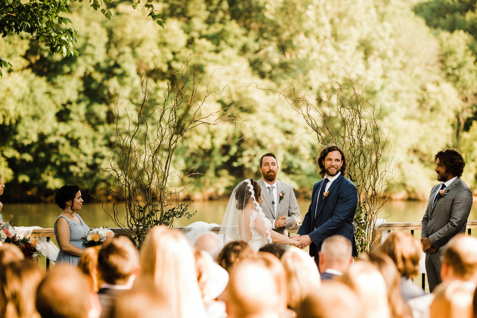 Groom laughs during Ceremony at Roswell River Landing