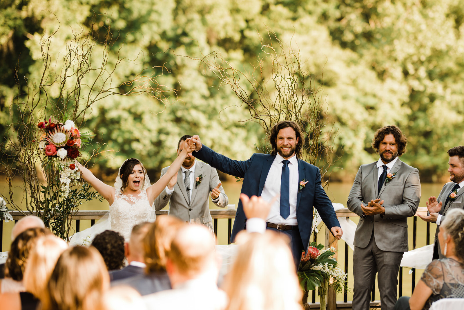 Bride and Groom cheer and walk down the aisle at Roswell River Landing