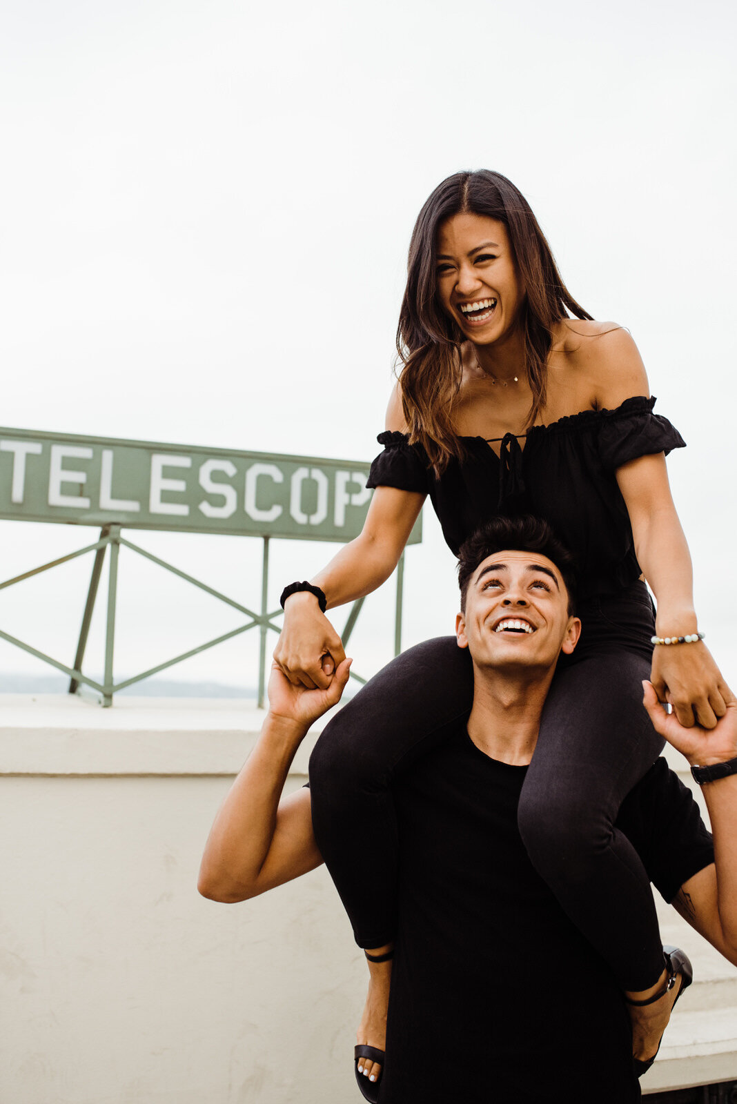 girl laughs on boys shoulders during Griffith Observatory dark and moody engagement session