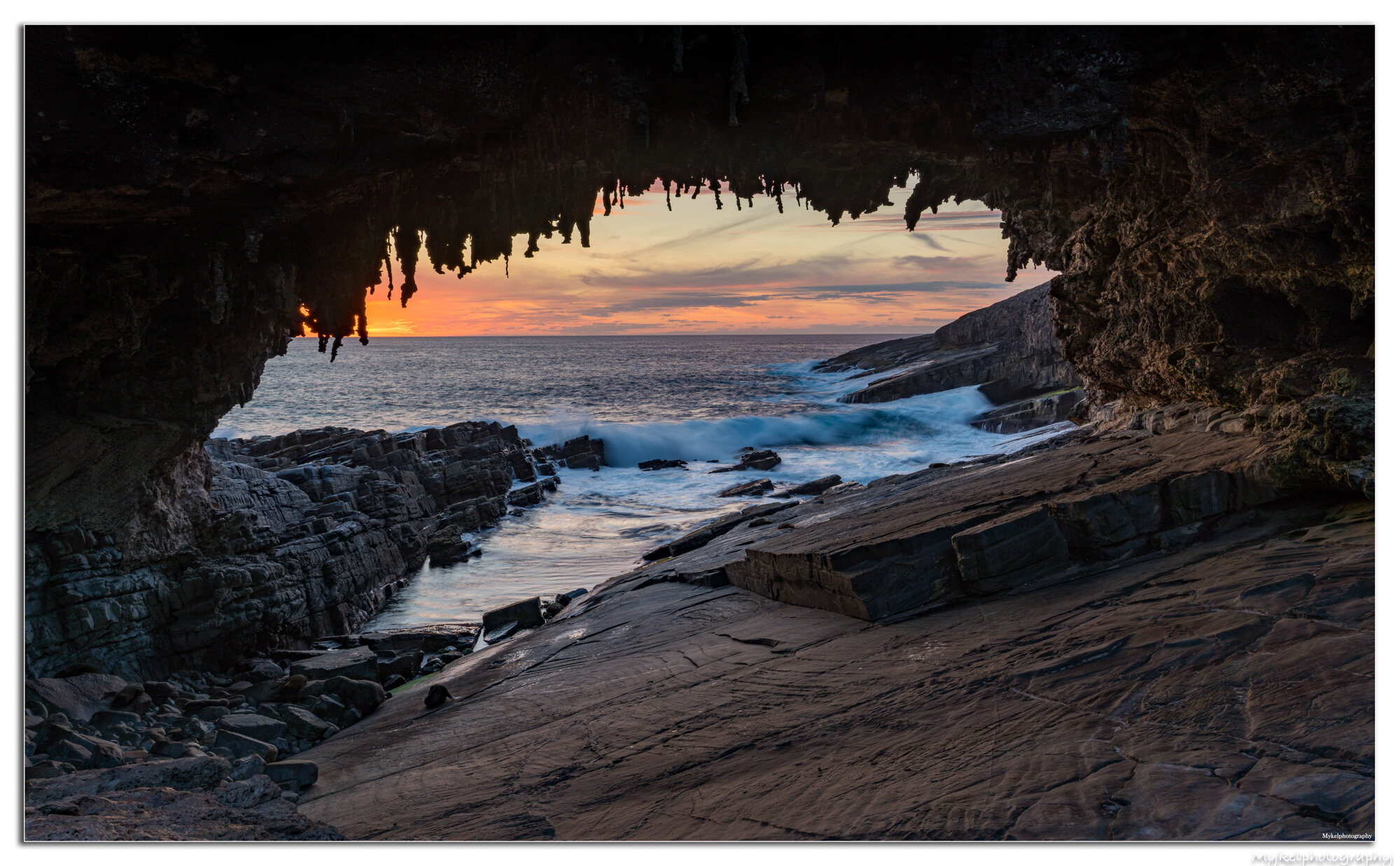 Admirals Arch is a natural rock arch created by amazing forces of nature. It's in Flinders Chase National Park on Kangaroo Island. You can take an easy walk on a boardwalk around the cliff face. This leads you to a viewing platform overlooking the arch. The arch is sculpted by weathering and erosion from the sea over thousands of years.